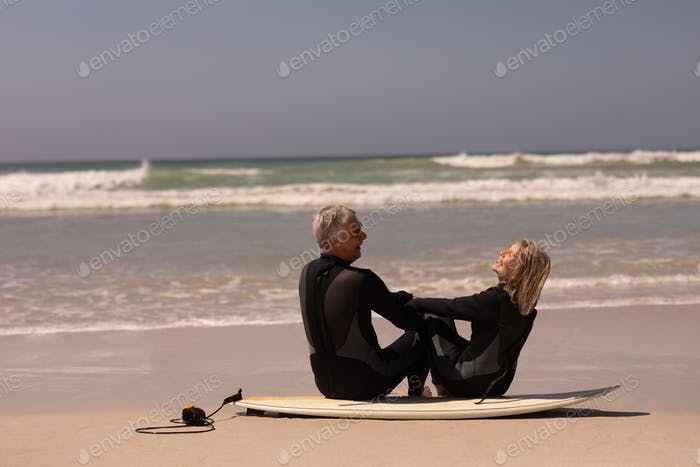 Side view of happy senior couple sitting on surfboard at beach in the sunshine 4k