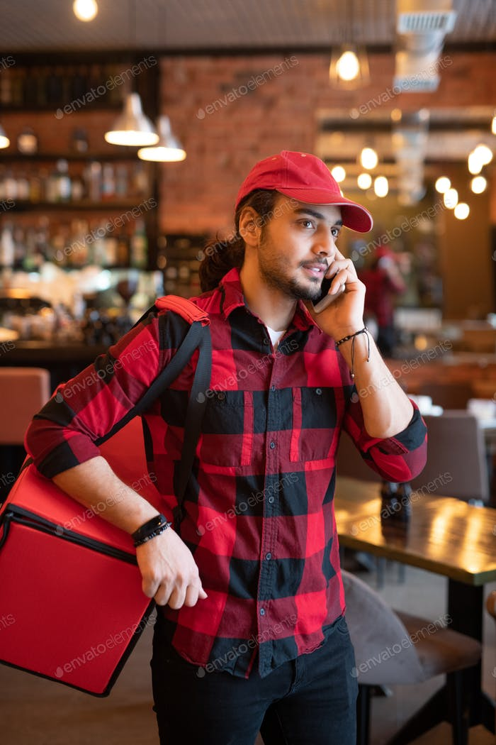 Young courier with big red bag on shoulder calling one of clients in cafe