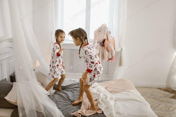 Zwei kleine Mädchen in ihren Pyjama haben Spaß springen auf einem Bett in einem sonnigen gemütlichen Schlafzimmer