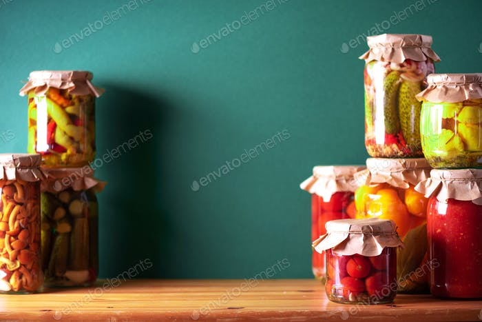 Preserved vegetables in glass jars on green background. Copy space. Healthy fermented food concept