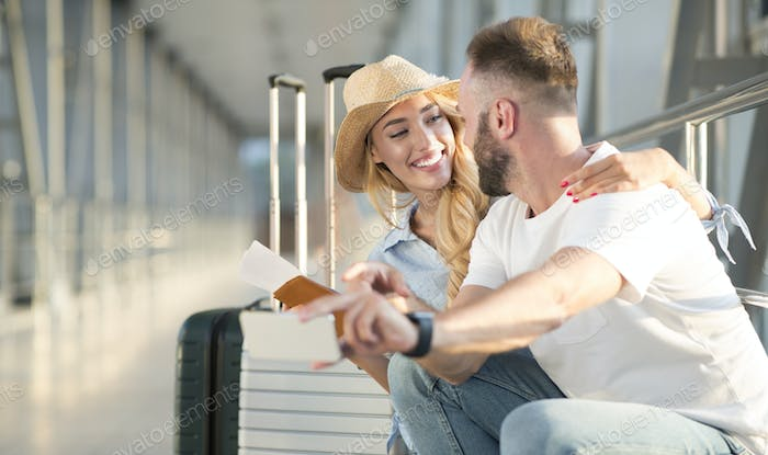 Loving couple in airport using travel app on smartphone