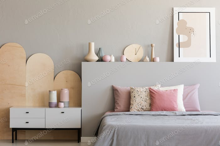 Pink pillows on grey bed in modern bedroom interior with poster