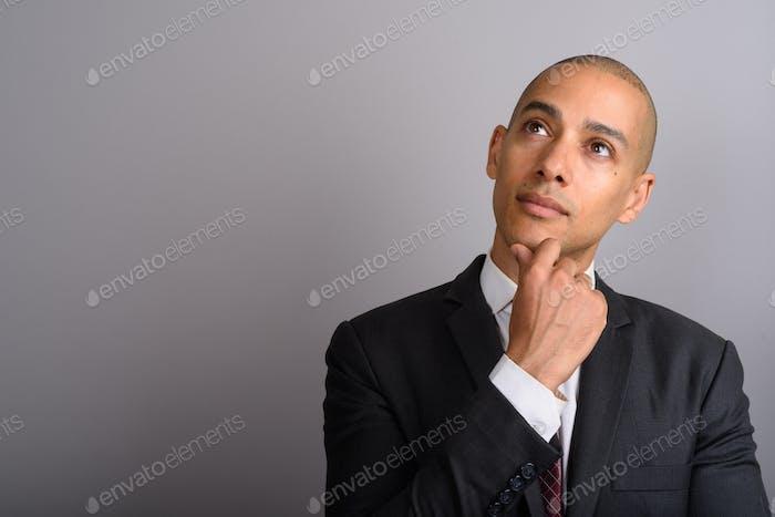 Красивый лысый бизнесмен думает и смотрит вверх