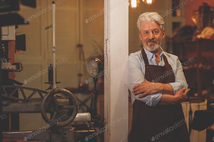 An elderly man an apron
