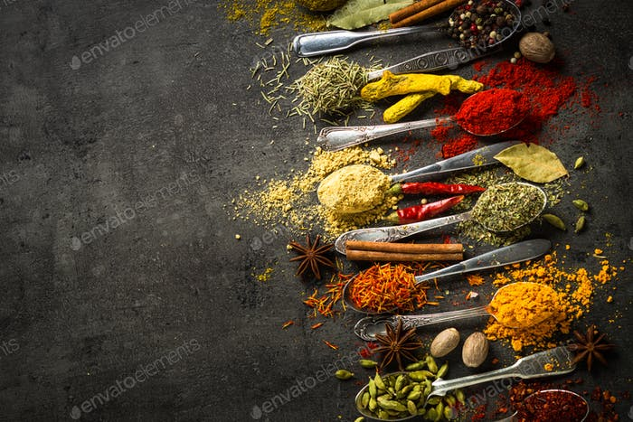 Set of various spices in spoons on black background.