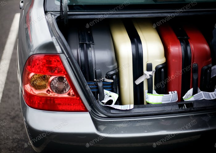 Suitcases in car trunk on street