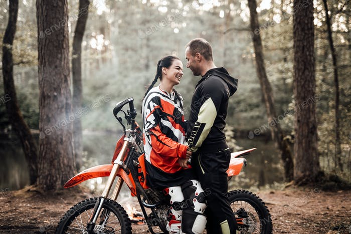 Attractive couple hold hands standing next to a motorcycle in the woods