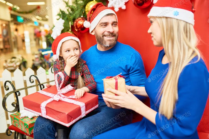 Cheerful family exchanging with presents in mall