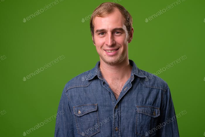 Young man against green background