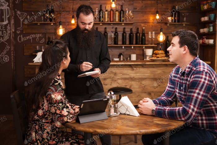 Frendly waiter is taking order from beautiful young couple