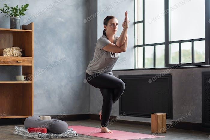 Junge Frau praktiziert Yoga, stehend in Adler Übung, Garudasana Pose
