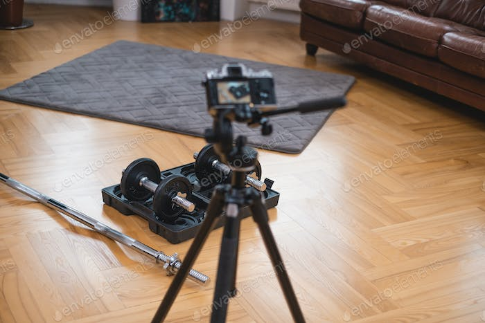 Photocamera shoots professional sports equipment on floor in room