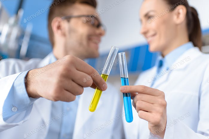 smiling scientists showing laboratory tubes, focus on foreground