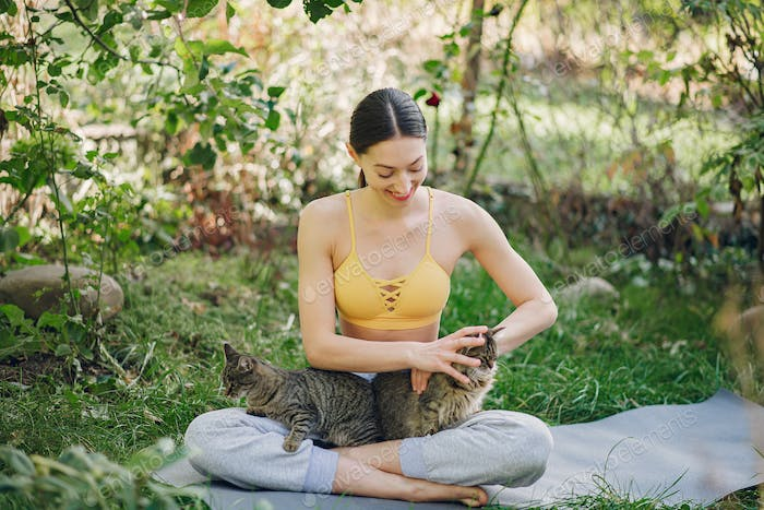 Girl sitting in a summer park with cute cat