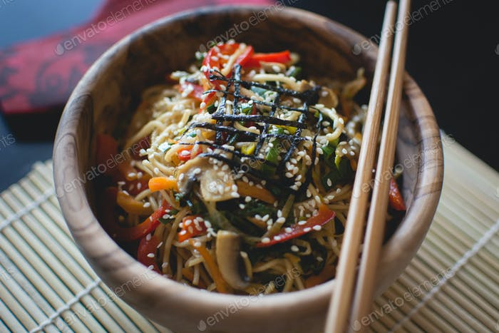 Noodles with vegetables in a wooden bowl with wooden chopsticks