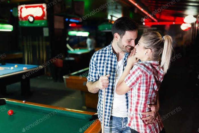 Young couple playing together pool in bar
