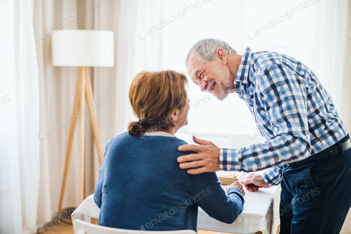 A senior couple sitting at the table at home, having breakfast.
