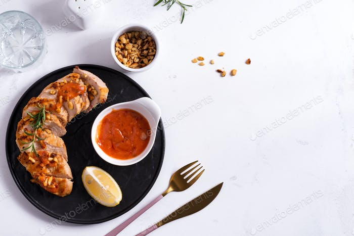 Grilled chicken breast with sauce, peanuts and lemon on a plate on stone background