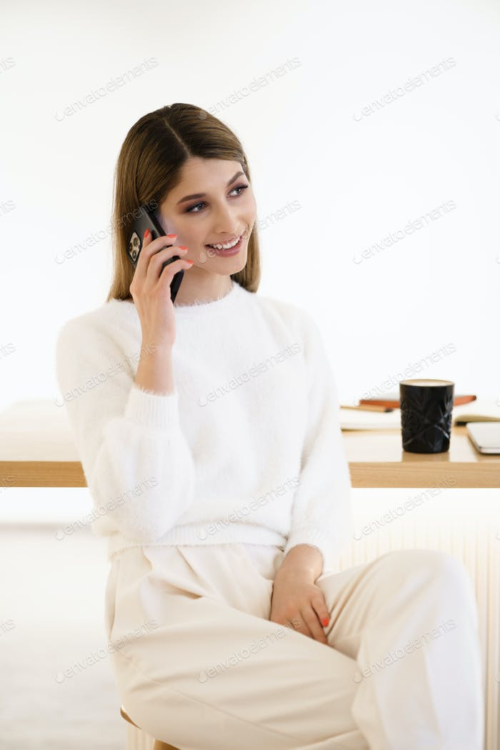 Smiling woman talking on the smartphone drinking coffee indoors