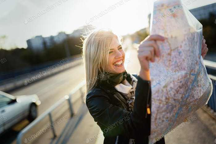 Young cheerful woman looking at map on bridge