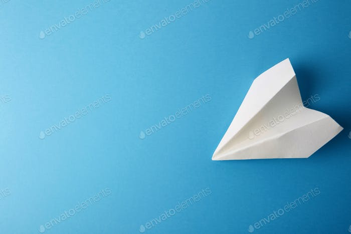 Flat lay of white paper plane and blank paper on pastel blue color background.Horizontal.