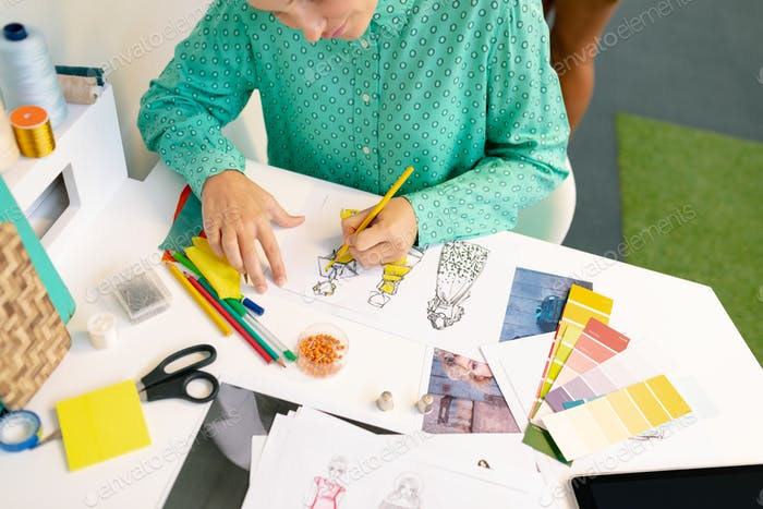 Mid section of Caucasian female graphic designer drawing a sketch in office