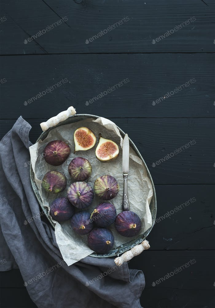 Vintage metal tray of fresh figs on dark background, top view, selective focus.