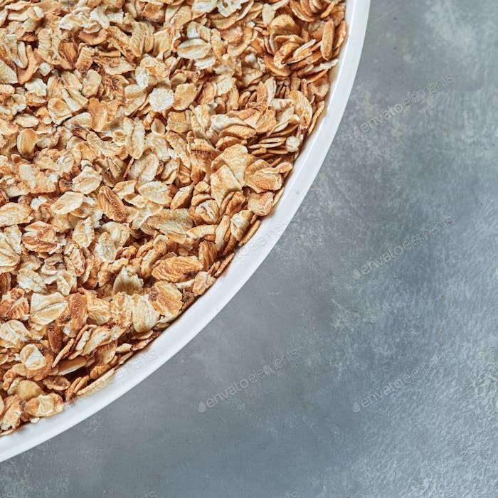 Nahaufnahme weiße Schüssel mit trockenen Haferflocken für die Zubereitung von gesundem Brei auf einem grauen Steinhintergrund