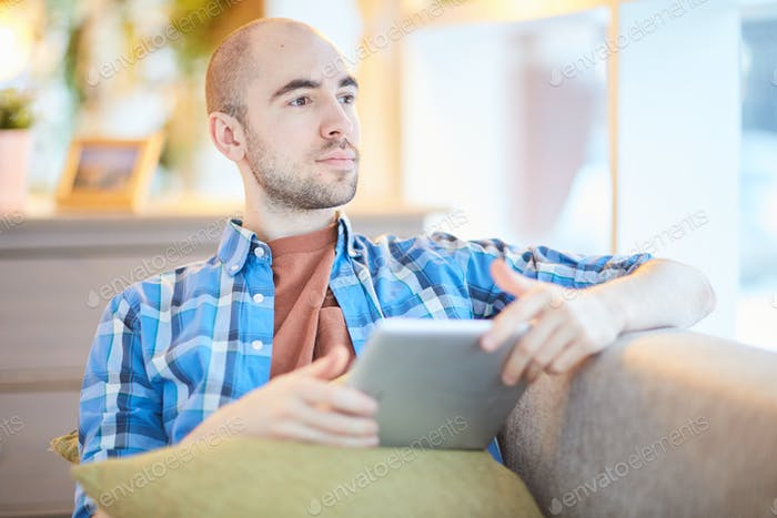 Pensive man with tablet