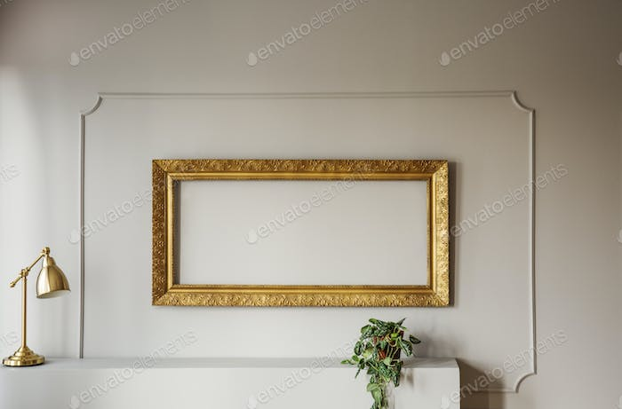 Elegant, empty golden frame inside molding on a gray wall of a s