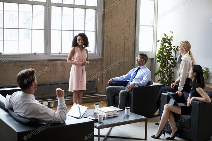 Female manager presenting at informal meeting in lounge room