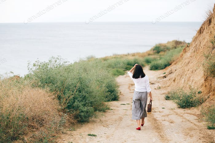 Elegante chica hipster relajante en la playa