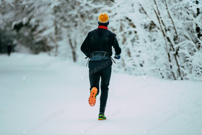 Male Athlete Running in Winter Woods