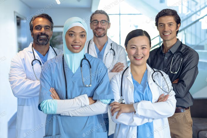 Happy diverse medical team of doctors standing with arm crossed and looking at camera