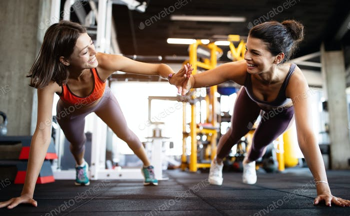 Beautiful fit people working out in gym together