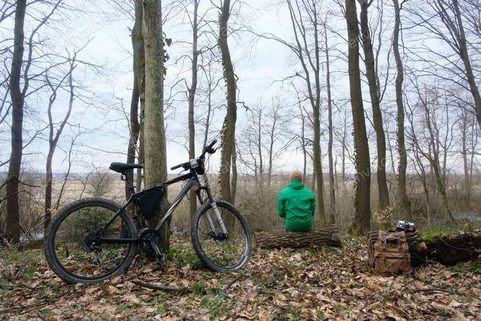 Man with bike in wild forest