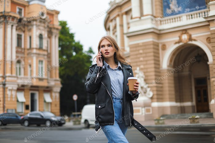 Young serious woman in leather jacket and jeans thoughtfully loo