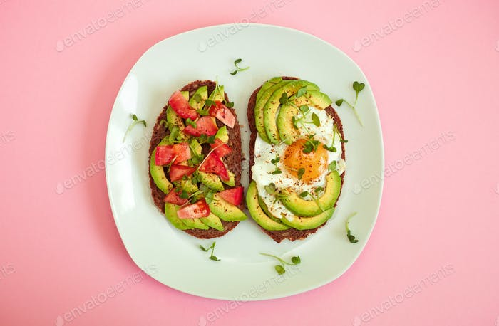 Two toasts of dark bread with avocado slices, chopped tomatoes, fried egg and microgreen.
