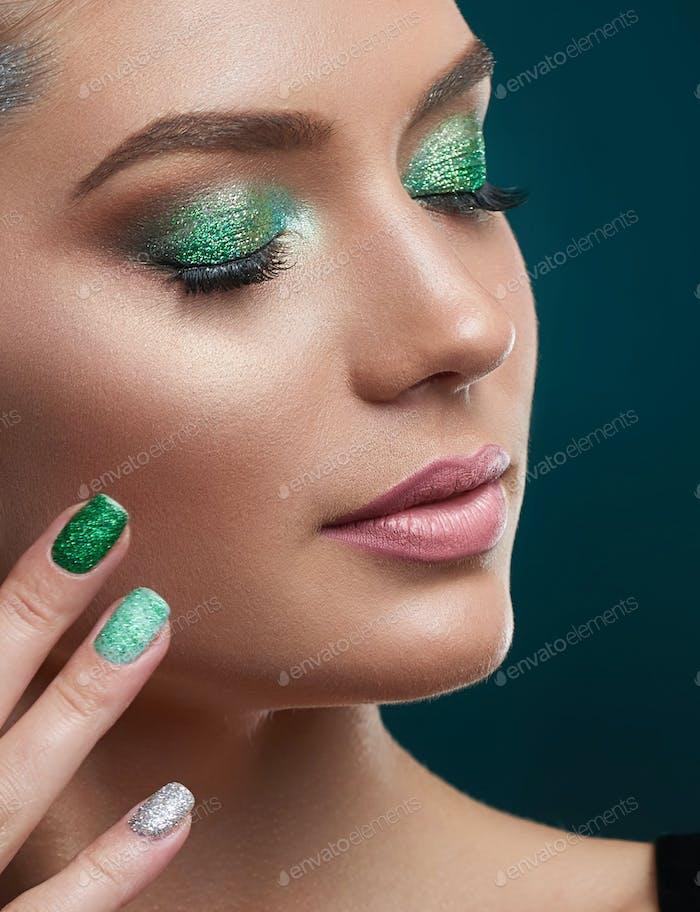Mädchen mit perfekter Haut, glänzende Maniküre, Make-up in grünen Farben