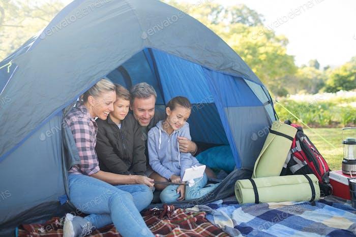 Familie mit einem Selfie im Zelt