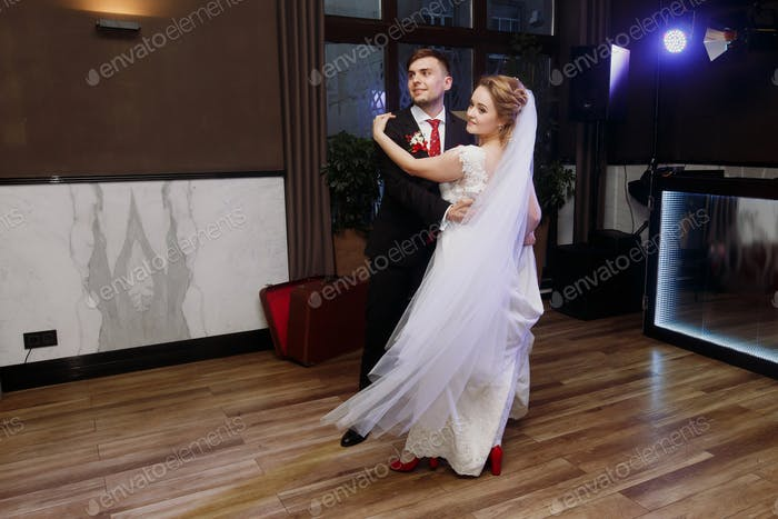 bride and groom dancing at wedding reception in restaurant