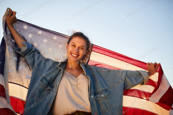 Excited young woman holding US flag