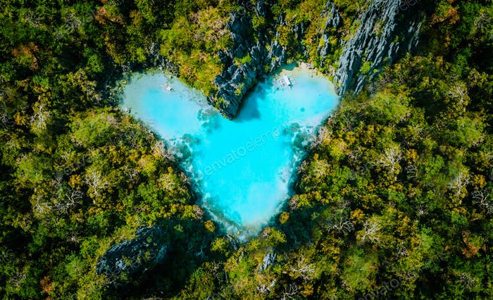 Aerial top view of turquoise lagoon shaped heart inside of tropical island. Love travel summer