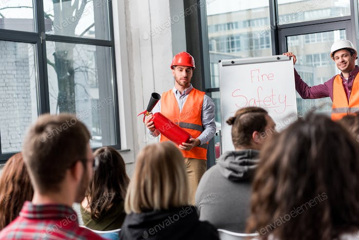 selective focus of handsome fireman in helmet holding extinguisher while standing near white board