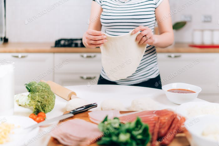 Close up details of pregnant woman preparing pizza and making dough