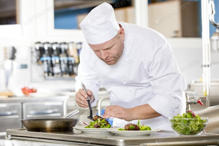Chef bereitet Steakgericht im Gourmetrestaurant
