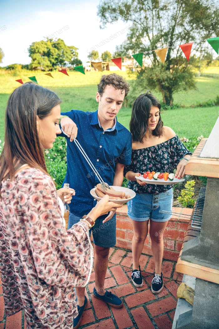 Group of friends cooking in a summer barbecue