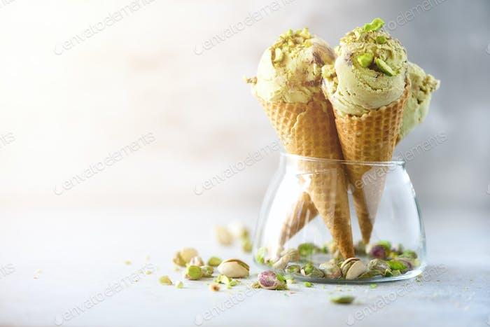 Grünes Eis in Waffelkegel mit Schokolade und Pistaziennüssen auf grauem Steingrund. Sommer