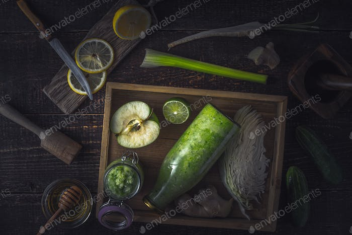 Bottle and jar with smoothie in the wooden tray  with different ingredients on the wooden table