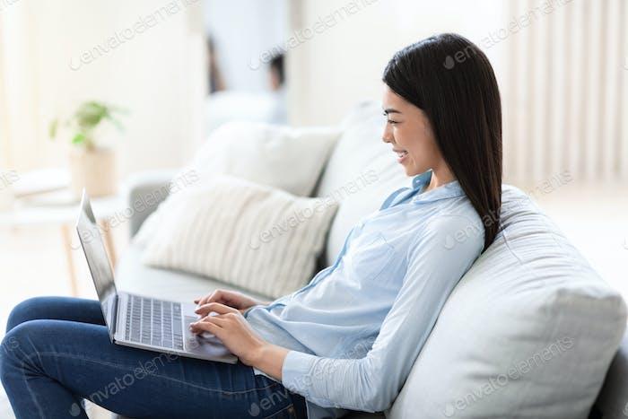 Remote-Büro. Lächelnde asiatische Freiberuflerin, die auf Laptop zu Hause arbeitet
